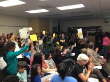 High School students hold up yellow thank you signs with teacher's names while their fellow student addresses the board.